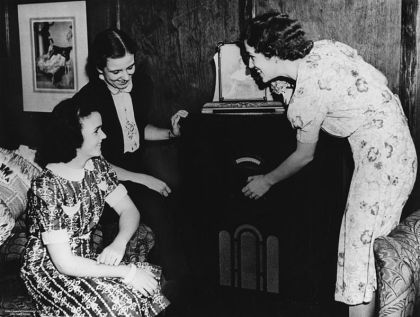 793px-StateLibQld_1_105248_Group_of_friends_gathered_around_a_radio_in_Brisbane,_ca._1942